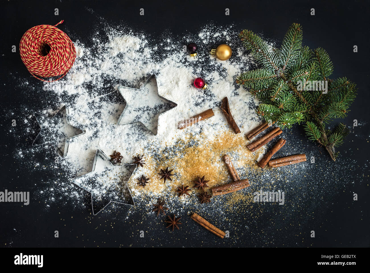 Cooking traditional Christmas holiday gingerbread cookies with cinnamon on black background - Stock Image