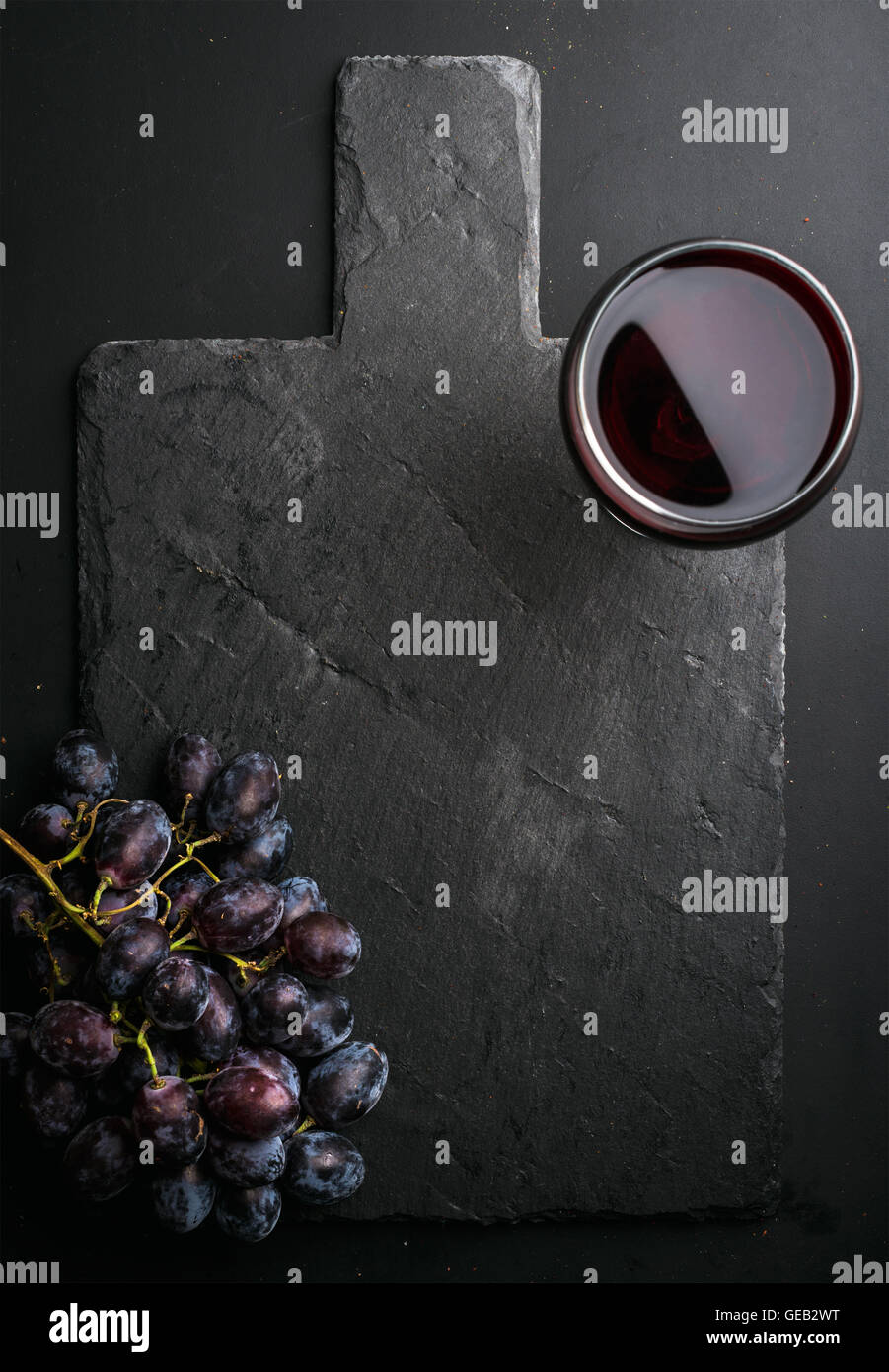 Glass of red wine and grapes on black slate stone board over dark background - Stock Image