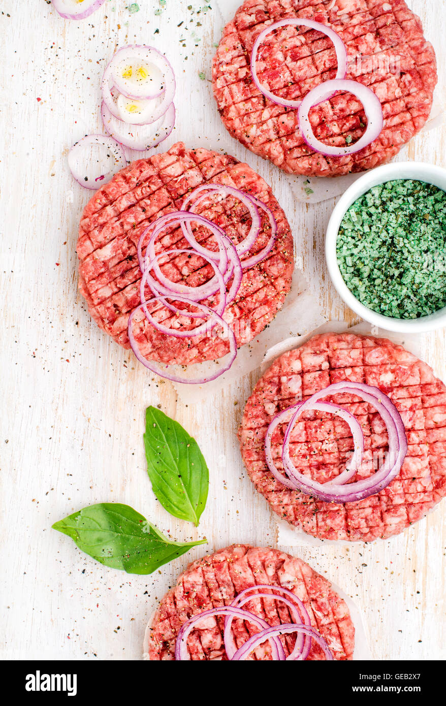Raw ground beef meat cutlet for making burgers with onion rings and spices on white wooden background - Stock Image