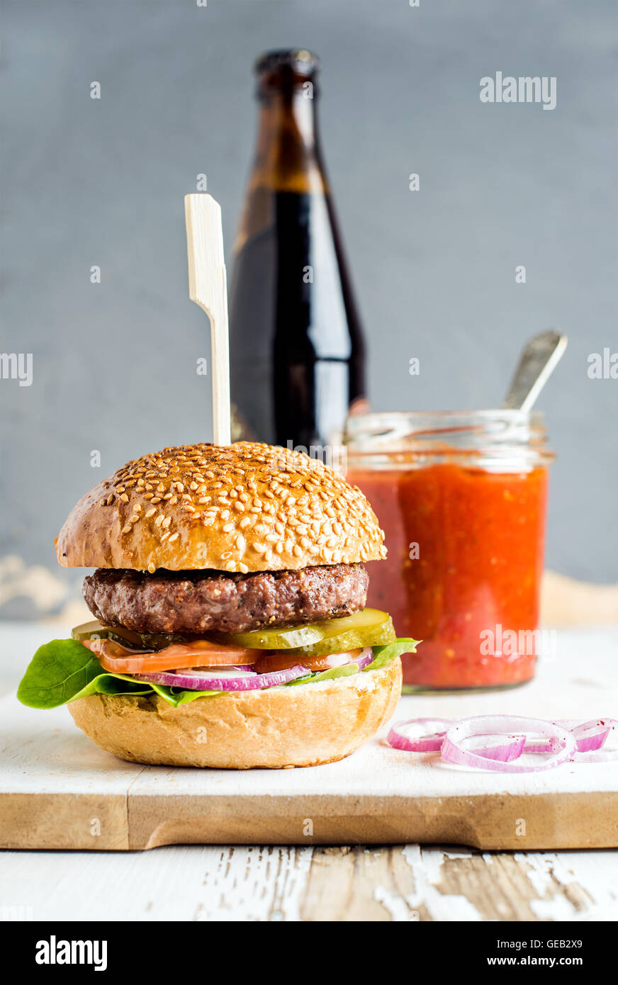 Fresh homemade burger on wooden serving board with spicy tomato sauce and bottle of dark beer, white background - Stock Image