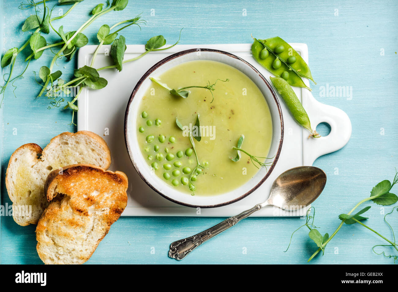 Light summer green pea cream soup in bowl with sprouts, bread toasts and spices - Stock Image