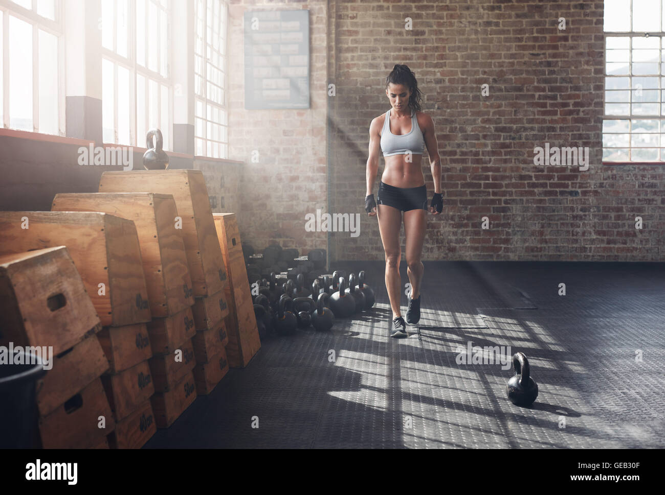Full length shot of fitness woman walking in the gym with kettle bell on floor. Female athlete warming up before - Stock Image
