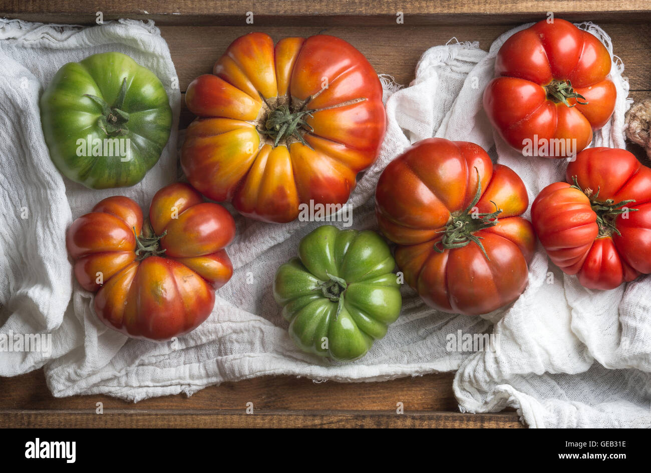 Colorful Heirloom tomatoes in rustic wooden tray - Stock Image