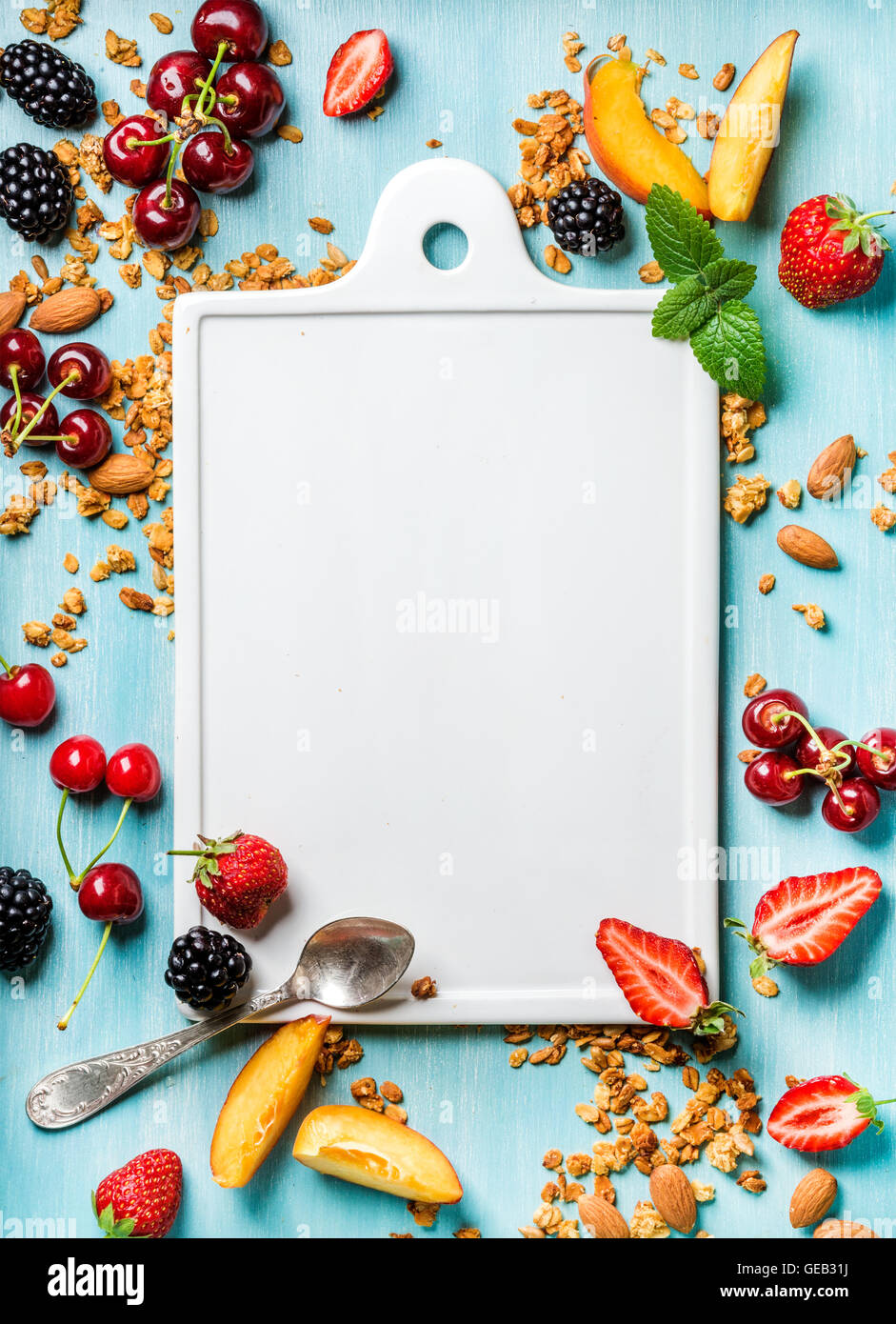 Healthy breakfast ingredients. Oat granola, fruit, berries and mint on blue background with white ceramic board - Stock Image