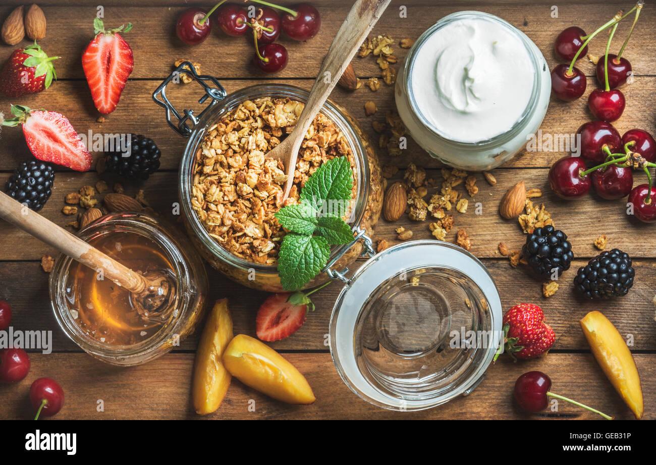 Healthy breakfast ingredients. Oat granola in open glass jar, fruit, yogurt, berries and mint over wooden background - Stock Image