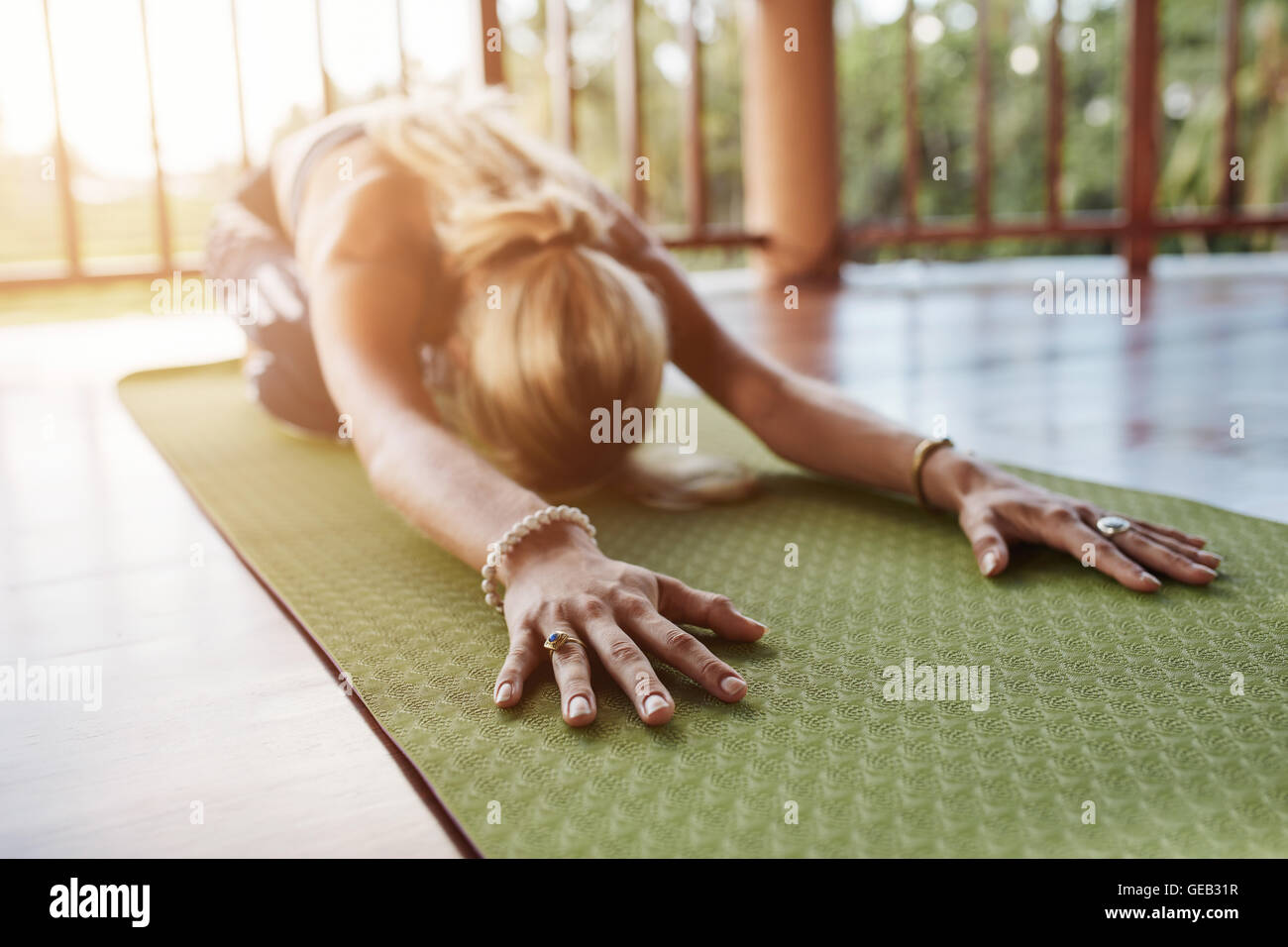 Woman stretching forward, performing a yoga pose on exercise mat. Fitness female performing balasana yoga at gym, Stock Photo