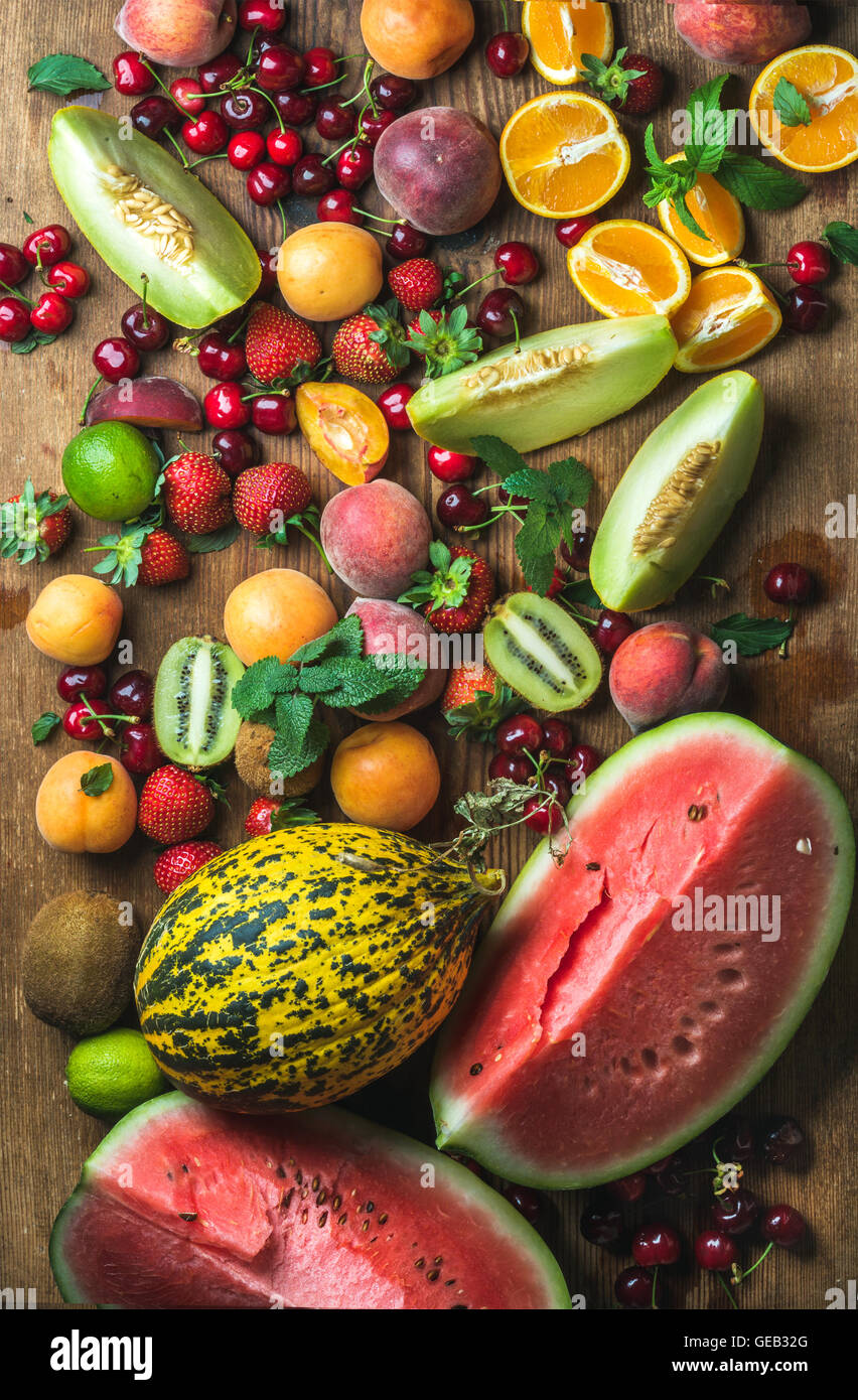 Various colorful tropical fruit selection on rustiv wooden background - Stock Image