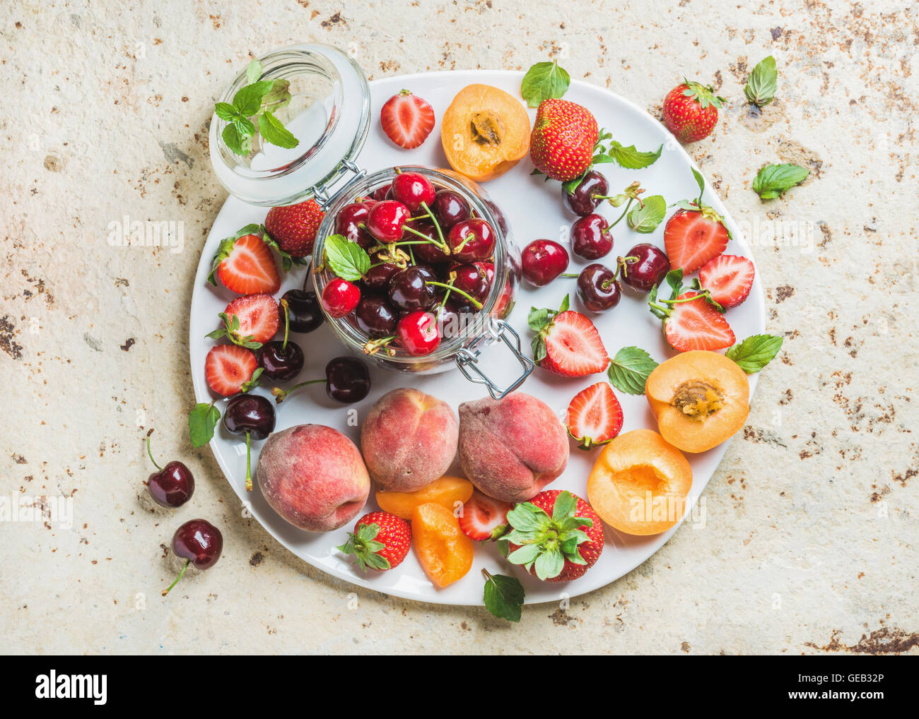 Healthy summer fruit variety. Sweet cherries, strawberries, peaches, apricots and mint leaves on white ceramic serving - Stock Image
