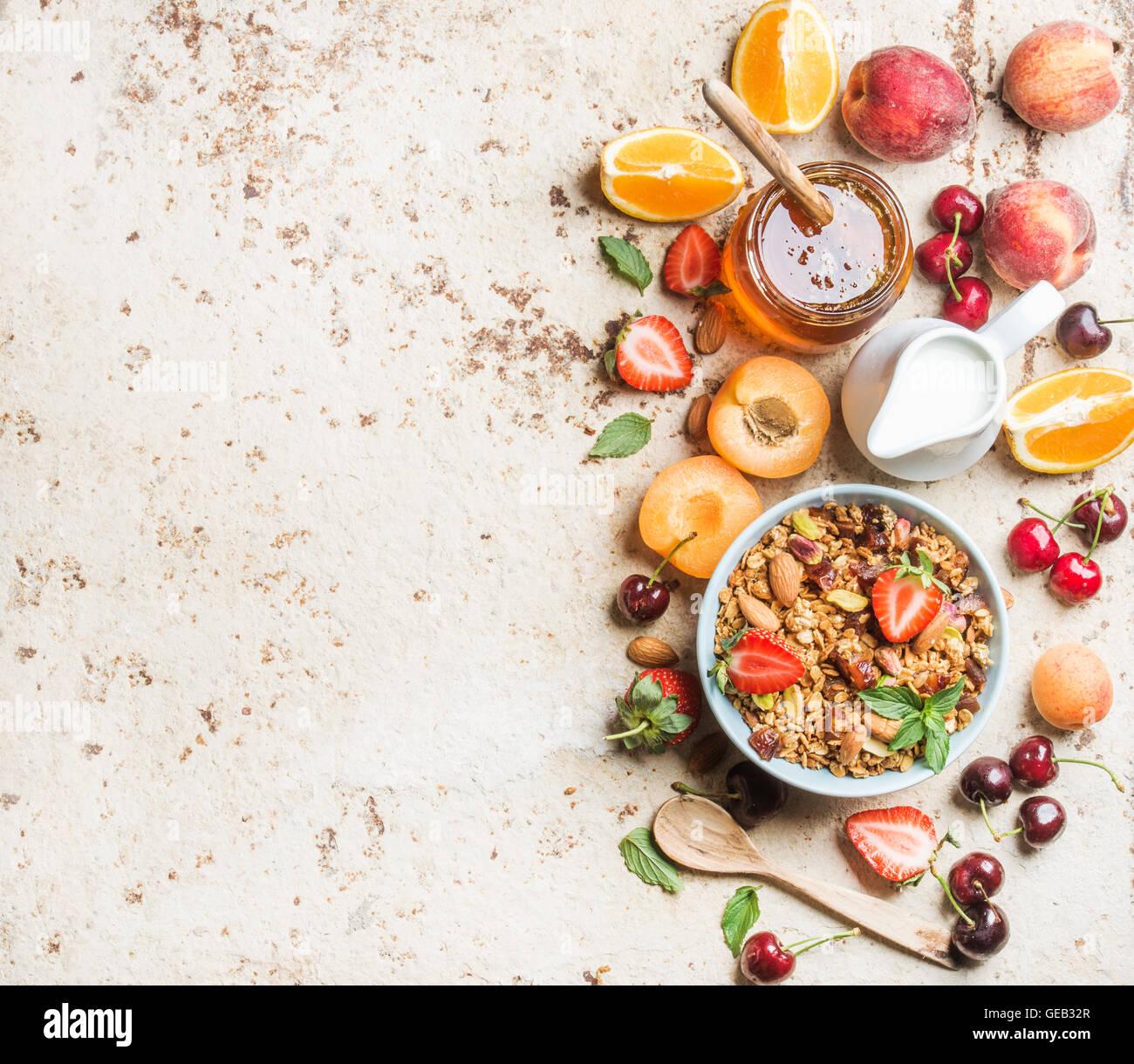 Healthy breakfast ingredients. Bowl of oat granola with milk, fresh fruit, berries and honey - Stock Image
