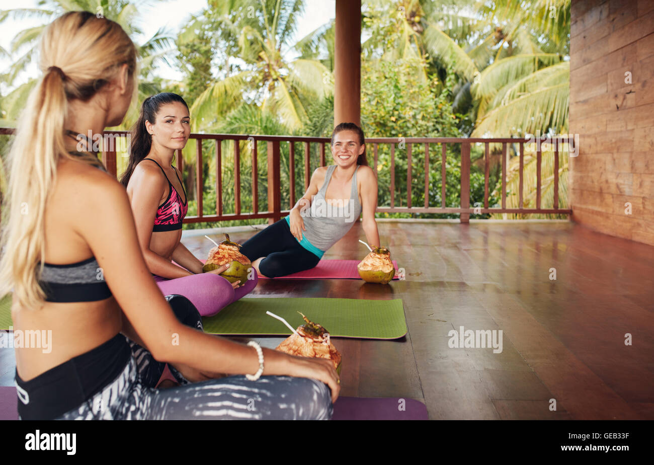 Women in yoga class taking break. Three beautiful girls relaxing with coconut juice and chatting after yoga session. - Stock Image