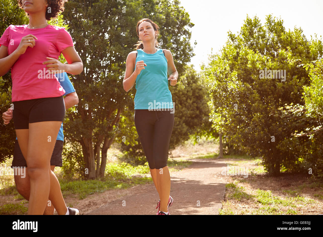 Group of three runners on a natural running trail in daylight surrounded by trees and bushes in the late morning - Stock Image