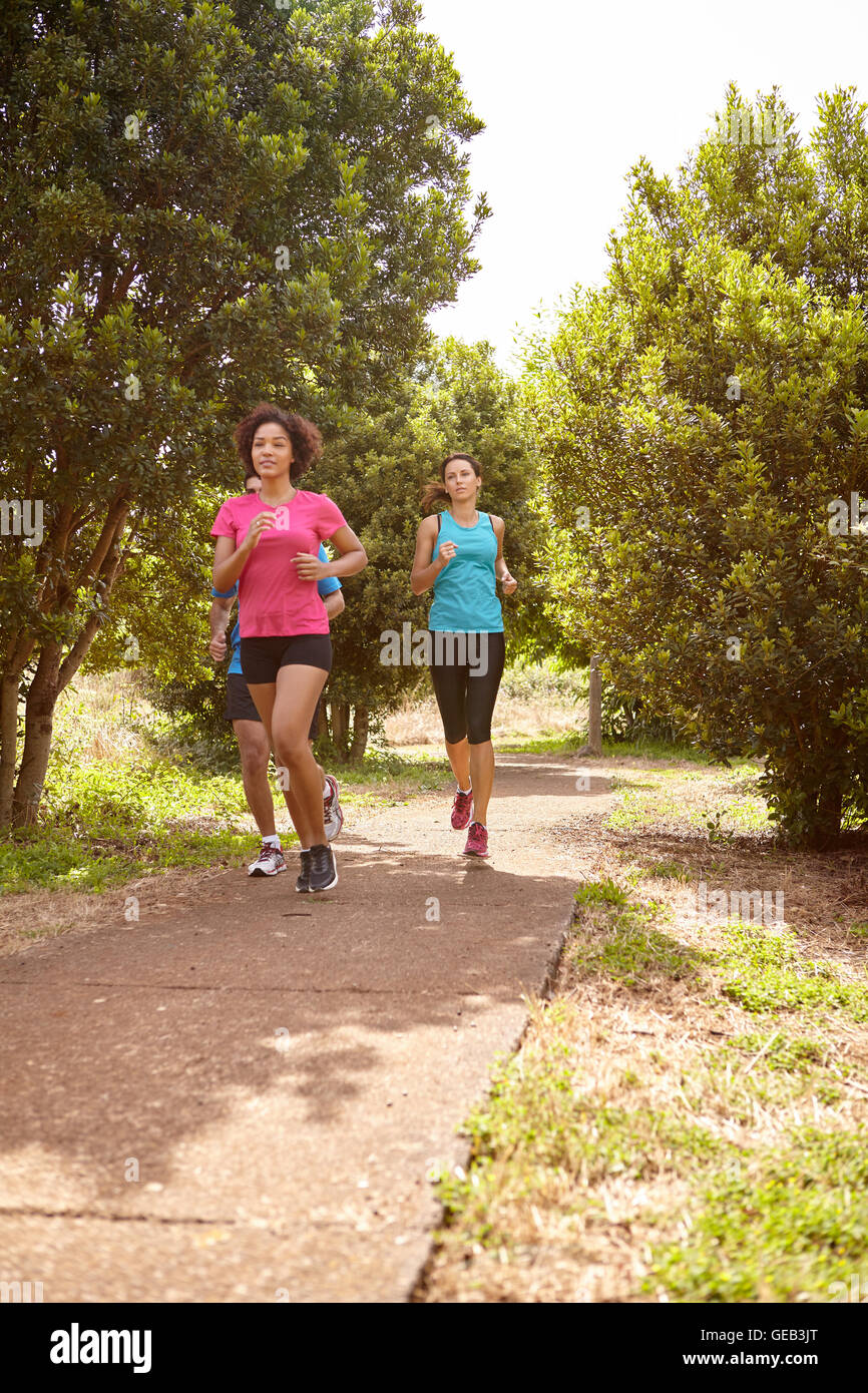 Three young runners on a paved jogging trail in daylight surrounded by trees and bushes in the late morning wearing - Stock Image