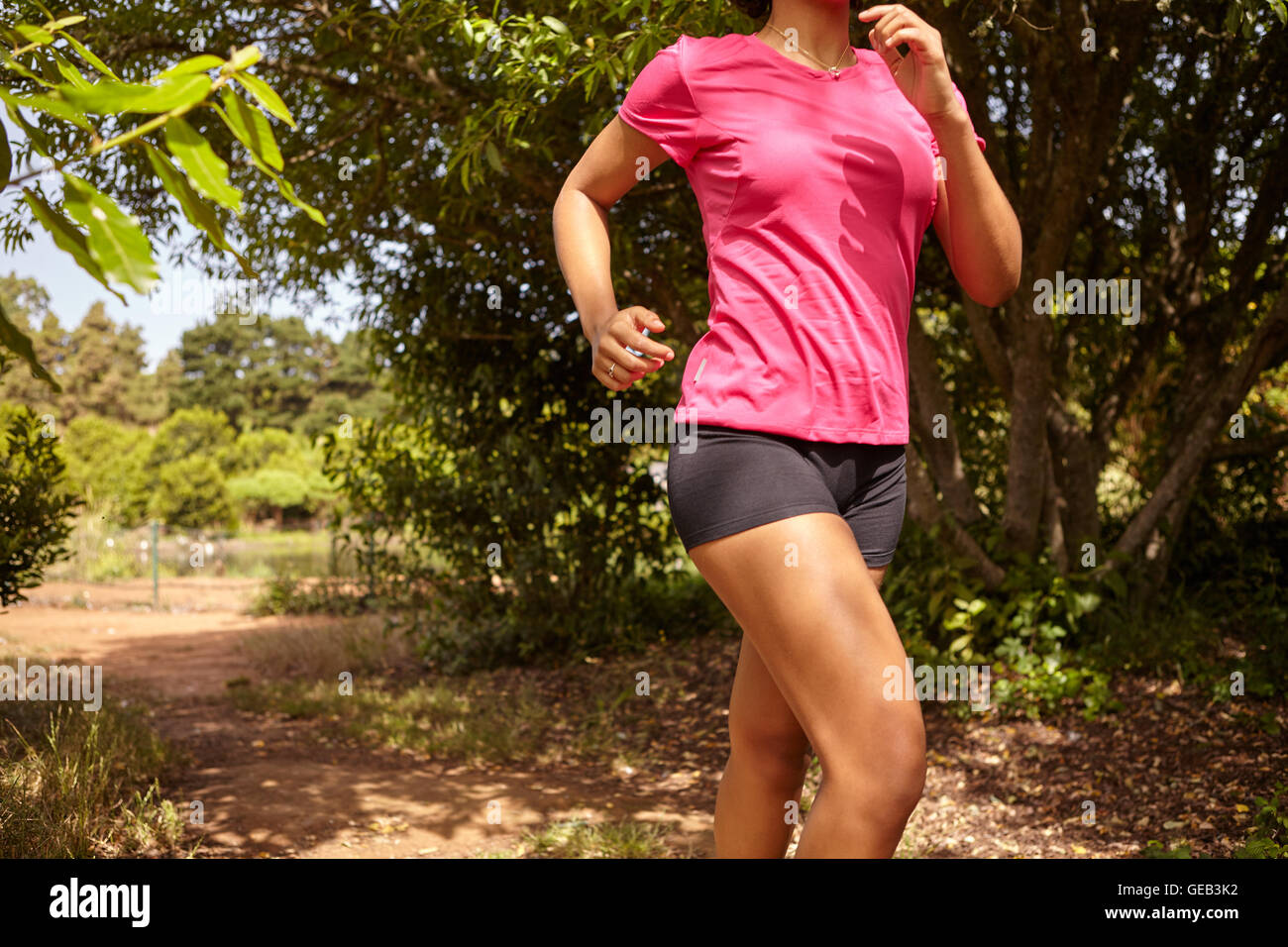 Female body showing from neck to knees running while wearing a pink t-shirt and black pants in a natural area surrounded - Stock Image
