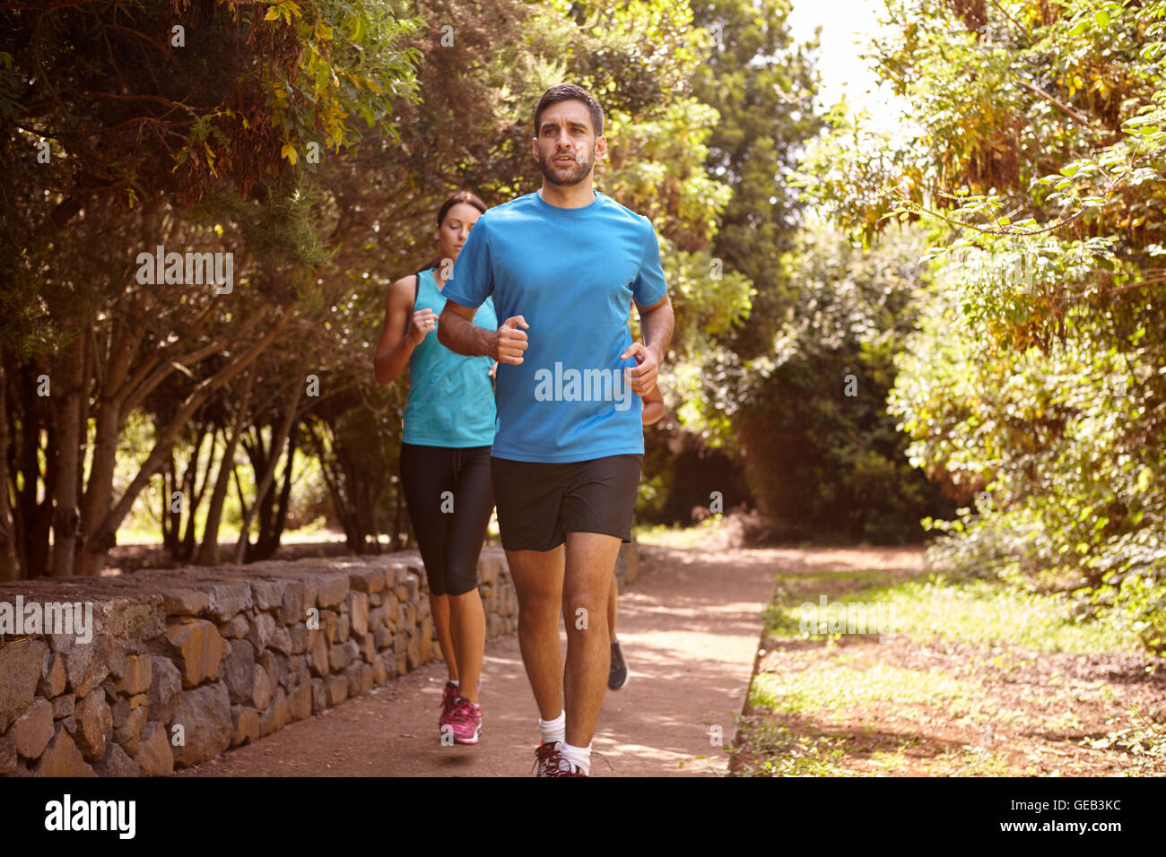 A guy and two girls running on a paved running trail with trees and a stone wall behind them wearing t-shirts and - Stock Image