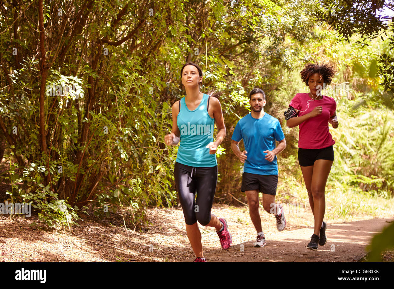 A young guy and two girls jogging on a gravel running trail with trees behind them while wearing t-shirts and black - Stock Image
