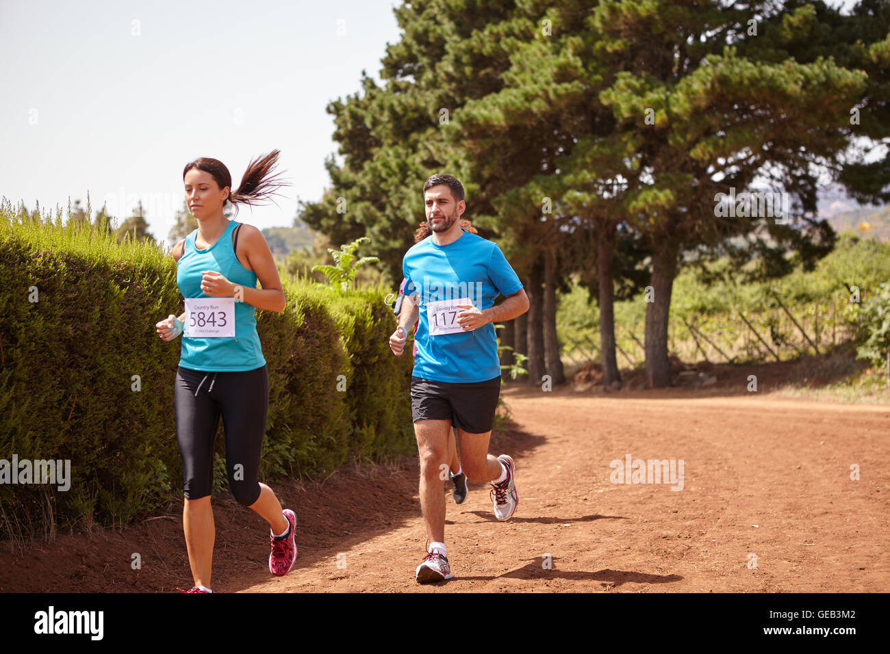 Three distance runners in a race on a gravel path with hedges behind them wearing casual running clothes in the - Stock Image