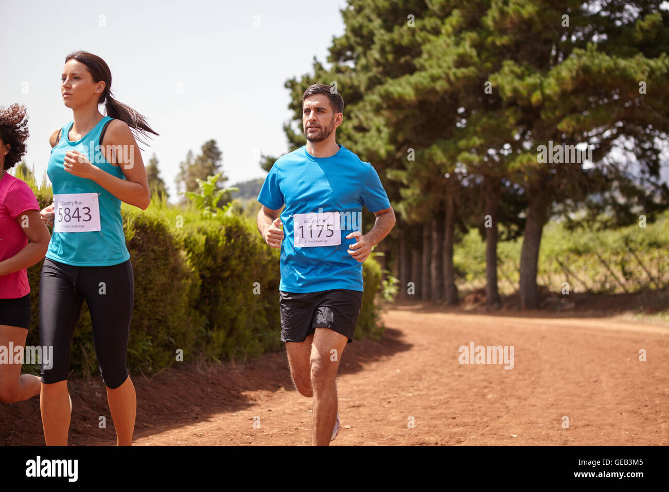 Three marathon runners in a race on a gravel path with trees behind them wearing casual running clothes in the late - Stock Image