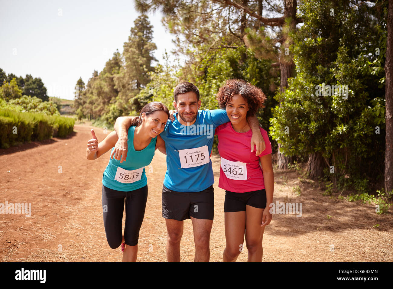 Three runners celebrating the end of a cross country marathon with trees behind them wearing casual running clothes - Stock Image