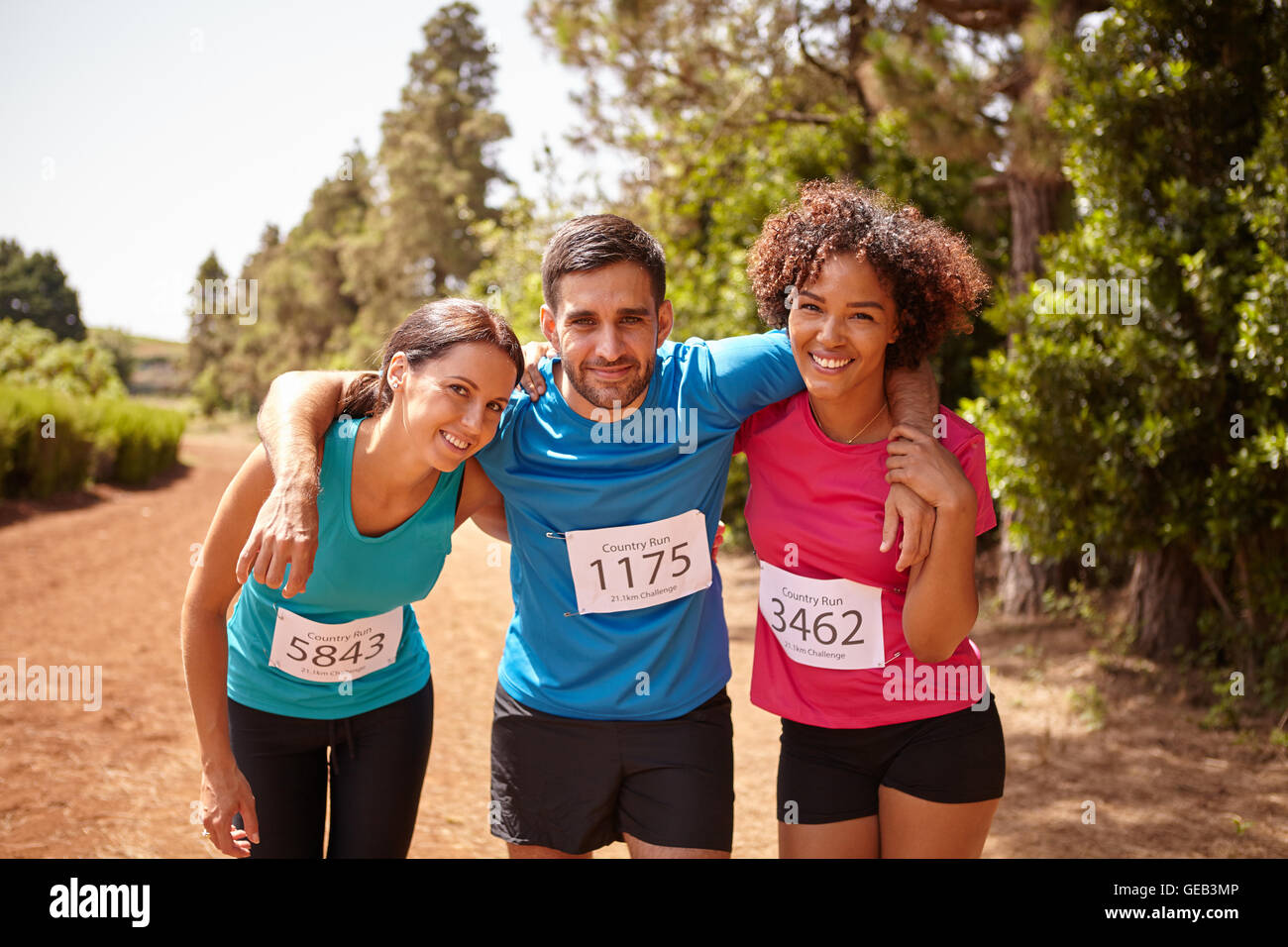 Three happy runners at the end of a cross country marathon with trees behind them wearing casual running clothes - Stock Image