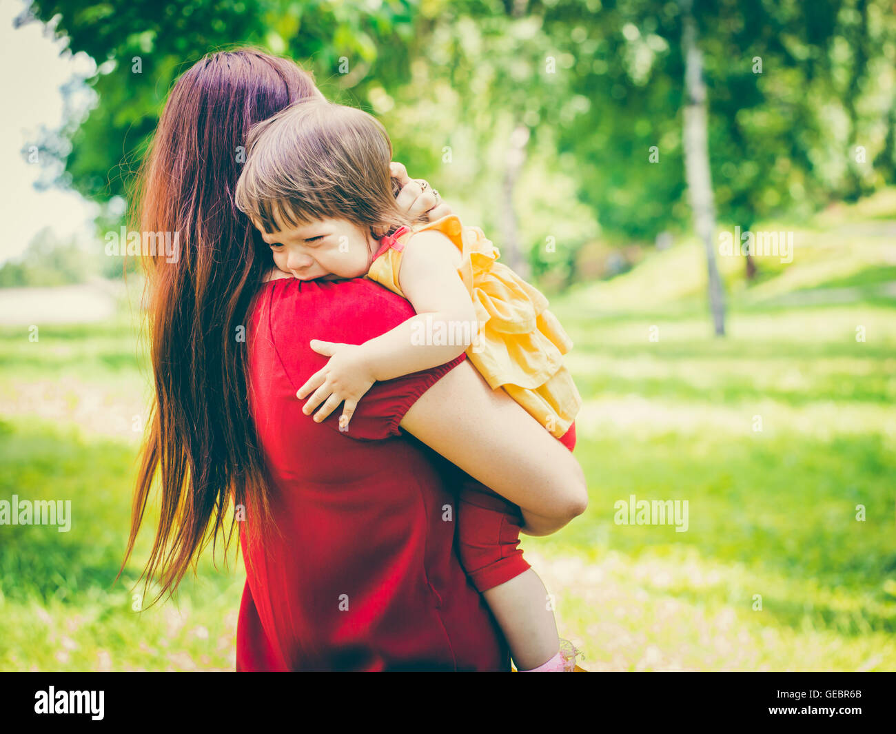 Mother holding her crying cute baby girl - Stock Image