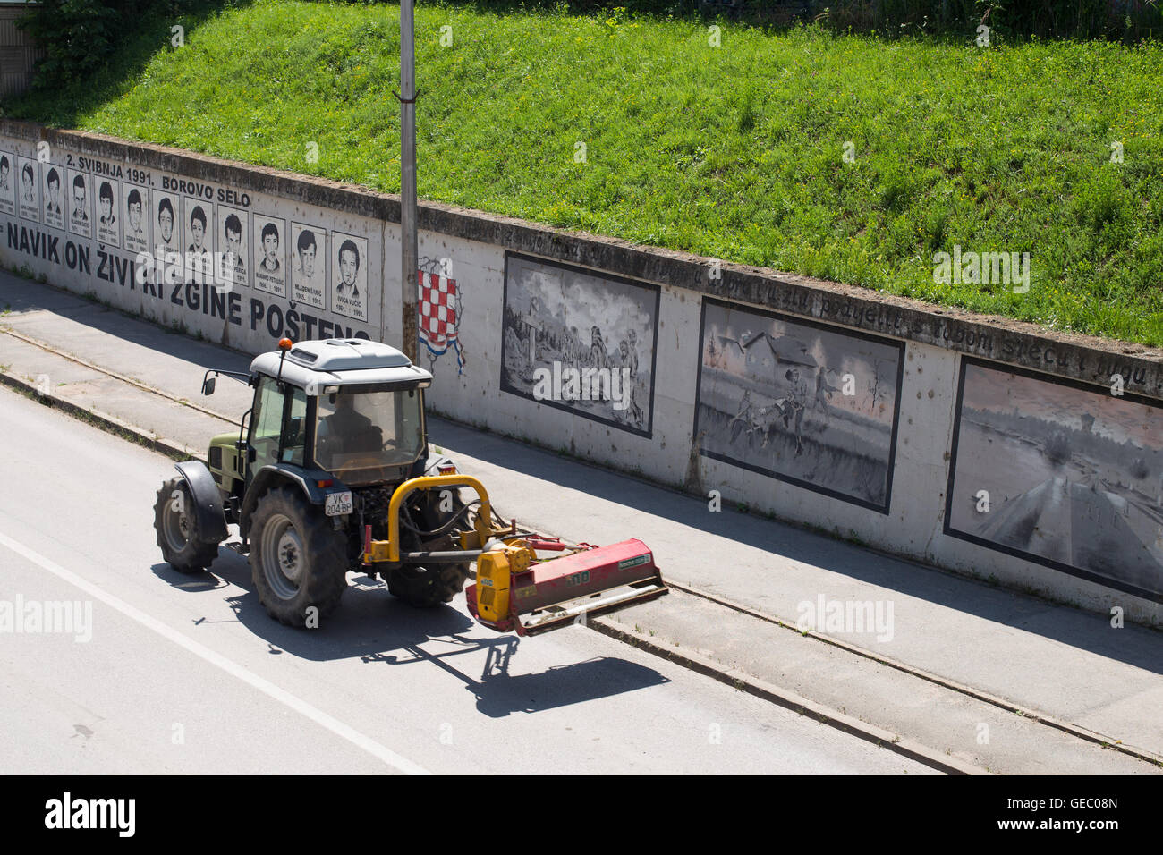 """A tractor passing in front of  Borovo Selo Memorial Wall: """"He Who Dies In Honesty – Lives Forever"""" - Stock Image"""