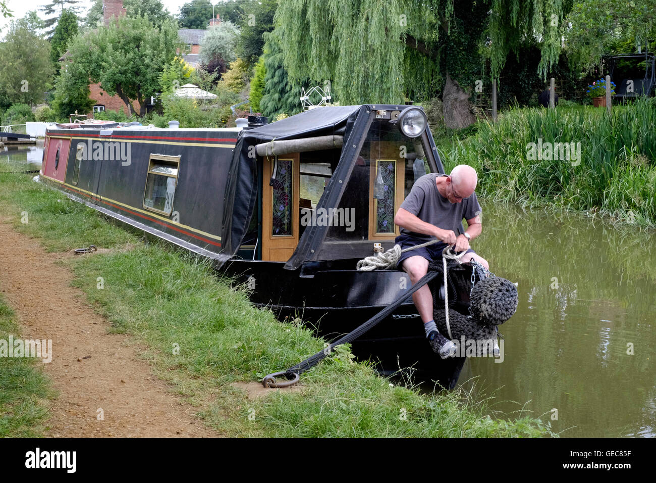 a man working on the bow of a boat on the oxford canal at cropredy near banbury england uk - Stock Image