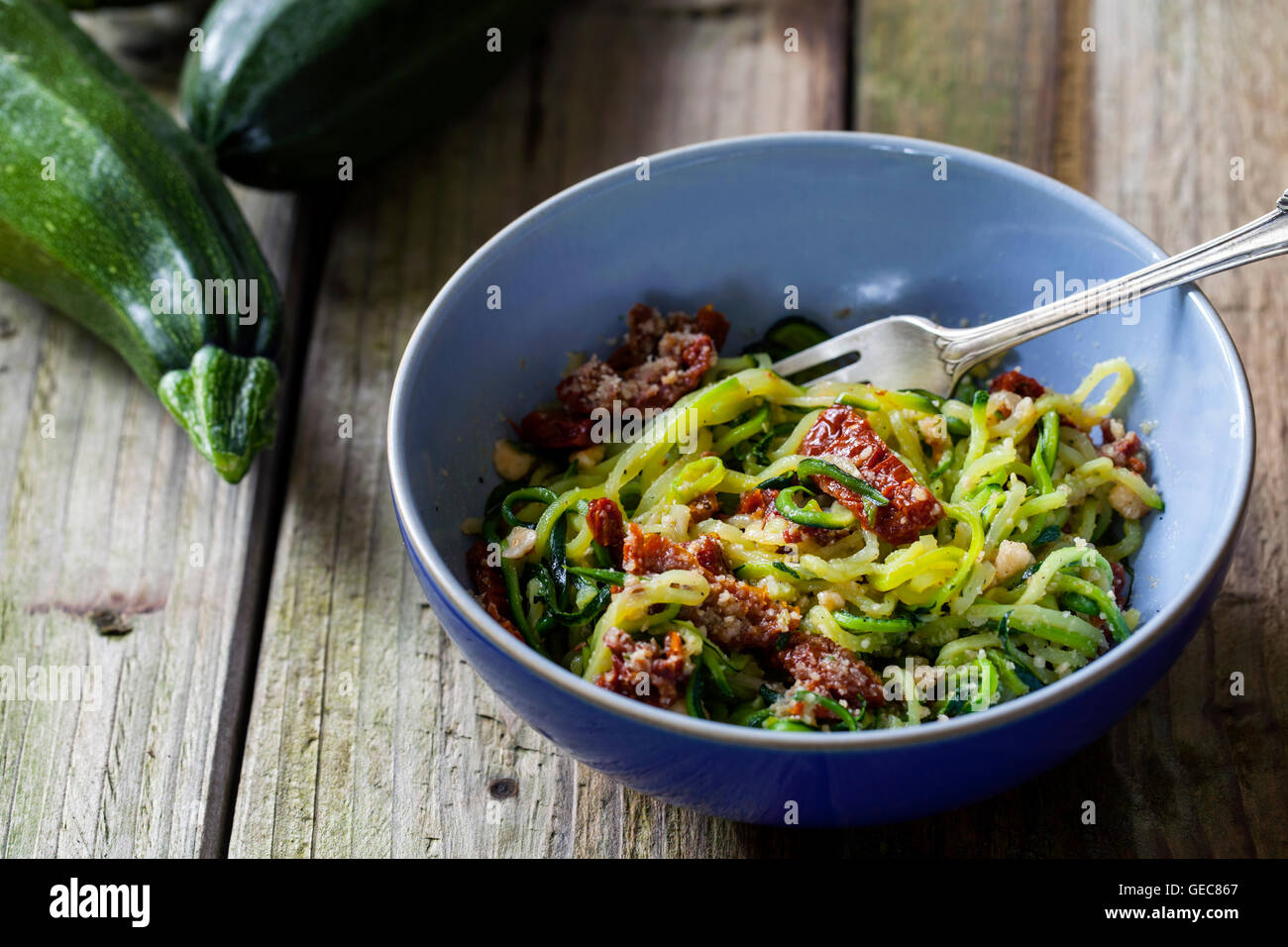 Courgette  spaghetti with sun dried tomatoes and mince hazelnuts Stock Photo