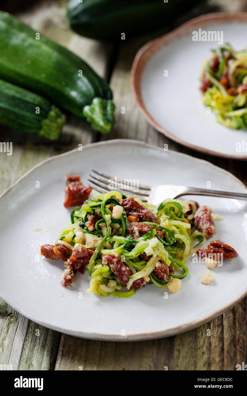 Courgette  spaghetti with sun dried tomatoes and mince hazelnuts - Stock Image