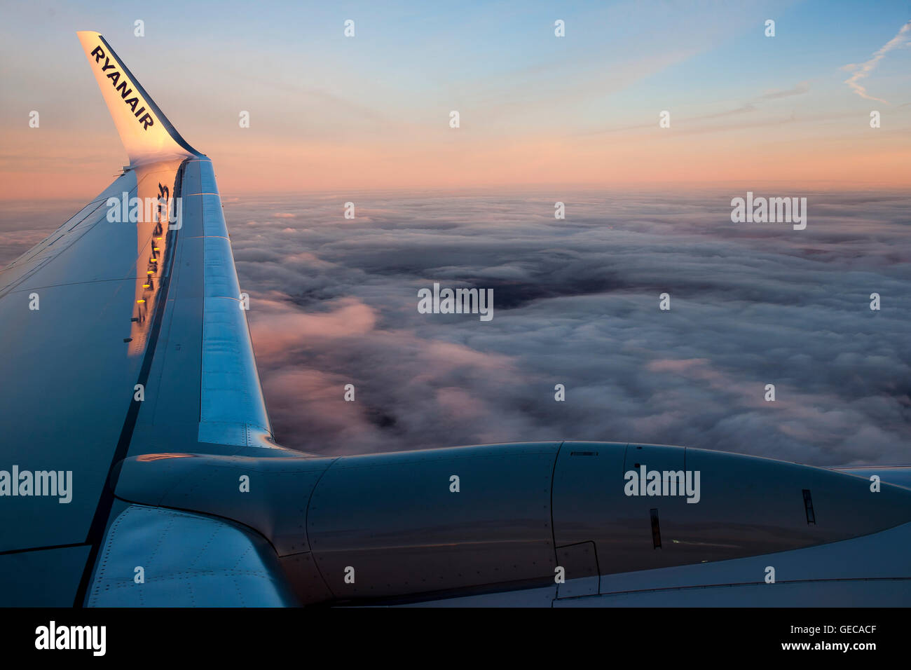 Sunset from the clouds across the winglet of a Ryanair plane as it flies from Liverpool to Riga on a scheduled flight. - Stock Image