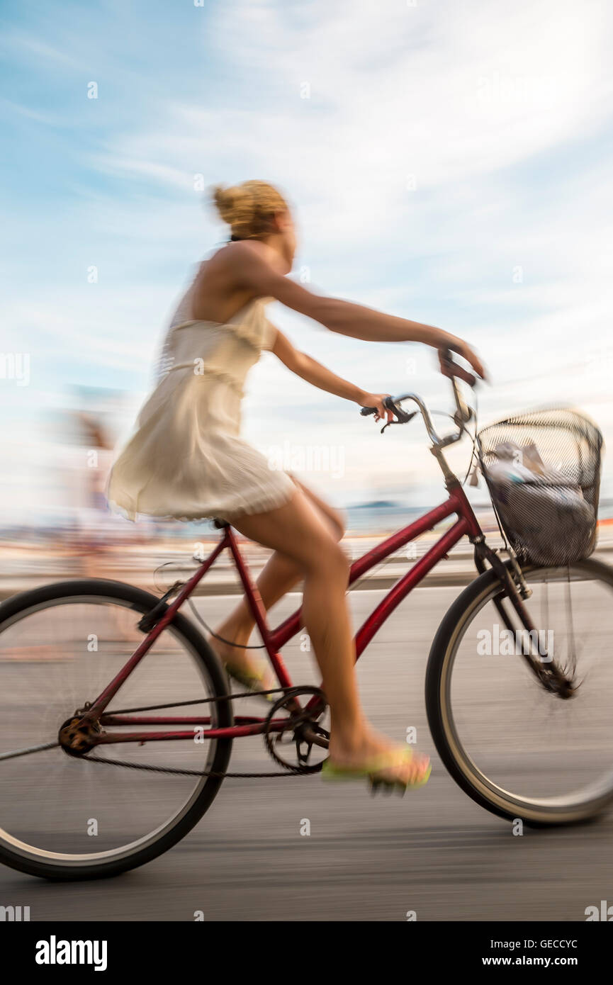 RIO DE JANEIRO - MARCH 6, 2016: A young Brazilian woman rides her bicycle in motion blur on the Ipanema Beach beachfront - Stock Image