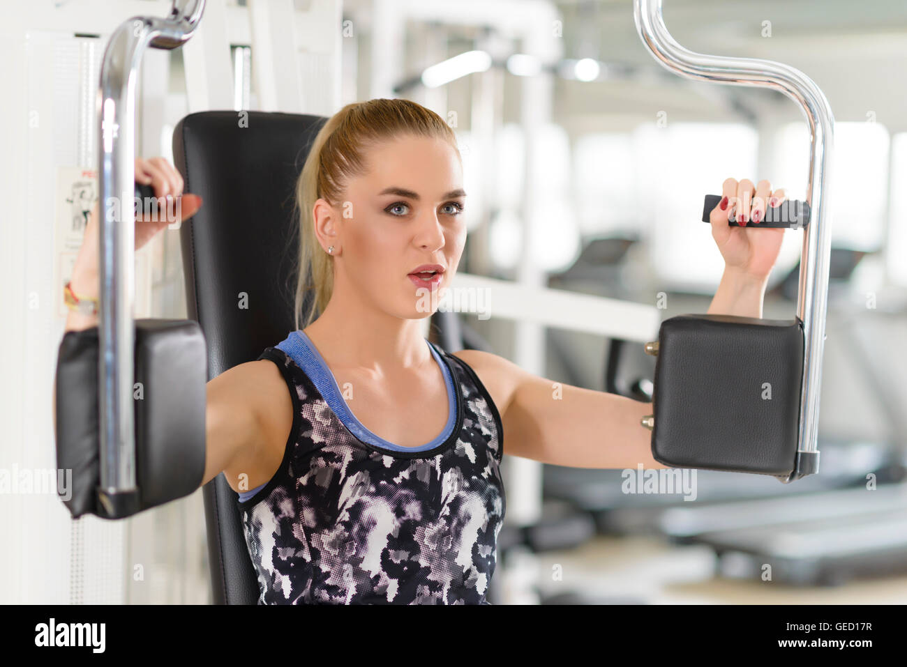 People using pectoral machine at gym - Stock Image