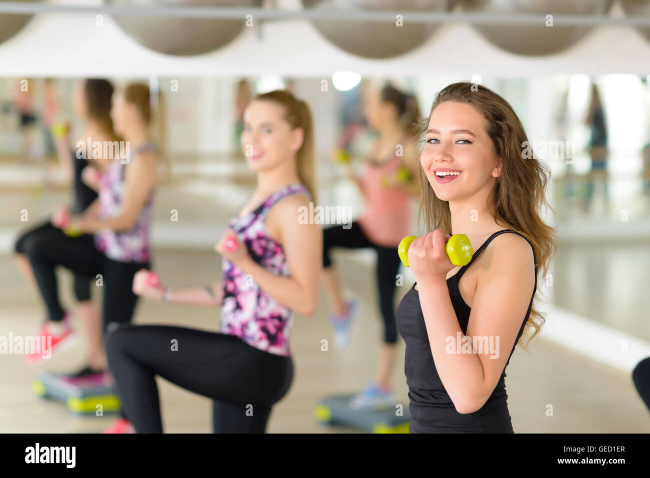 People exercising with dumbbell at gym - Stock Image