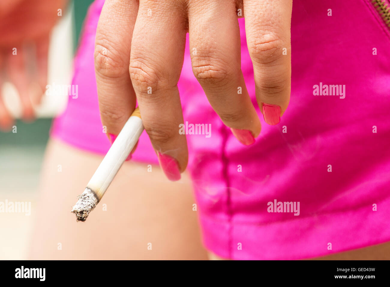 A woman holding a cigarette in her hand - Stock Image