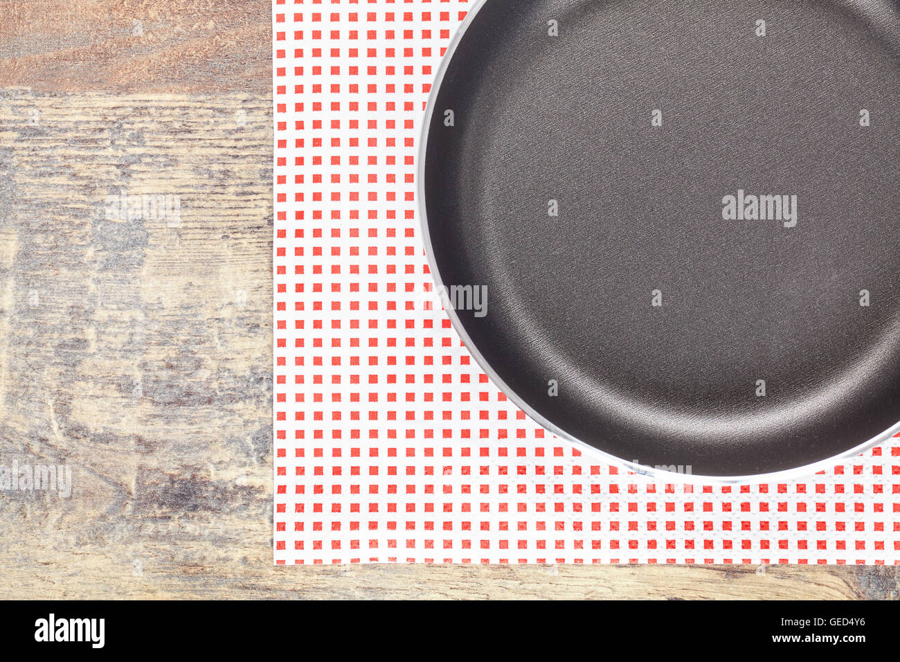 Top view of new empty frying pan on a napkin and wooden table, kitchen background. - Stock Image