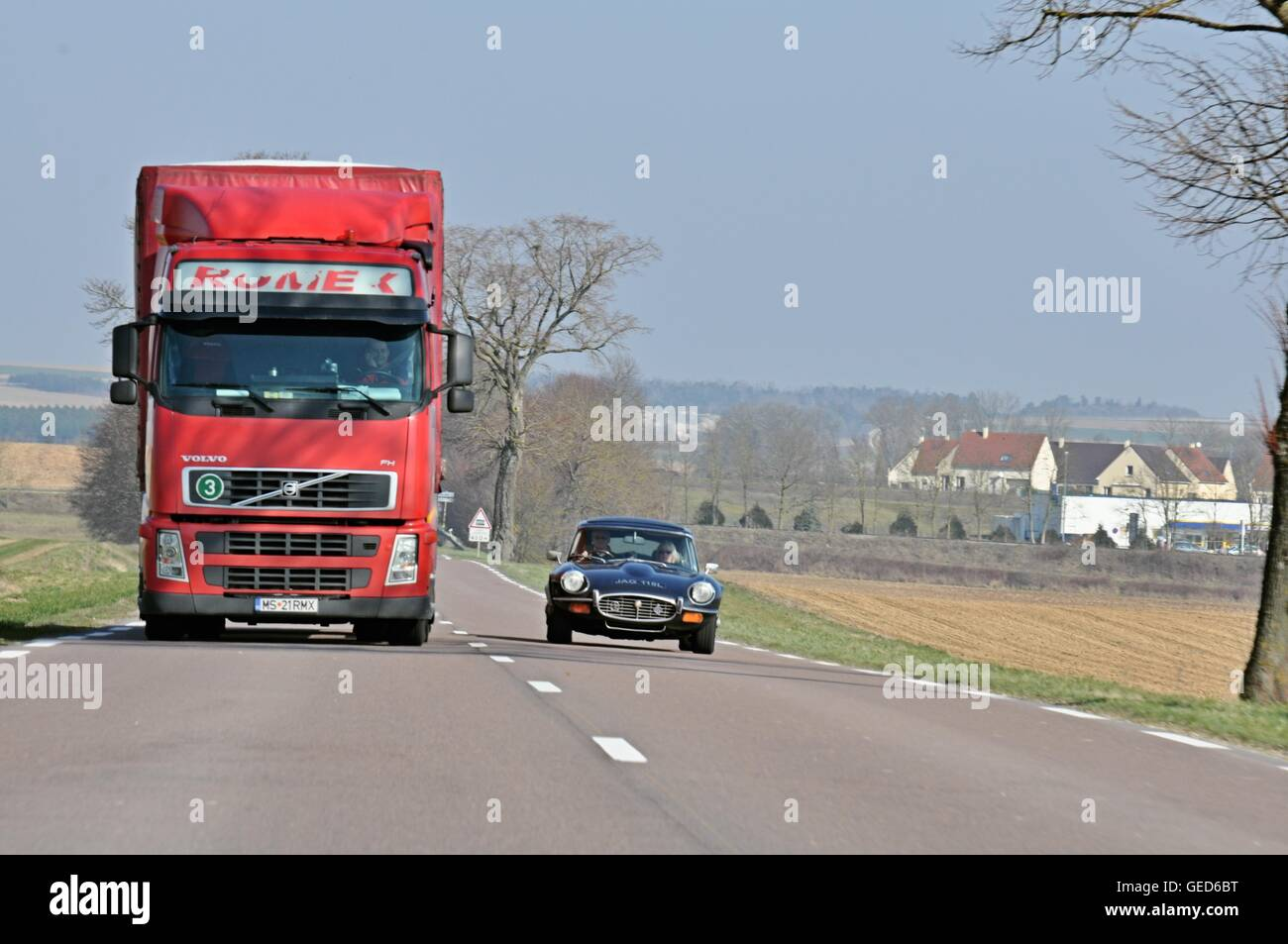 Jaguar E-type classic car overtaking a large red articulated lorry on a clear road in the French countryside in - Stock Image