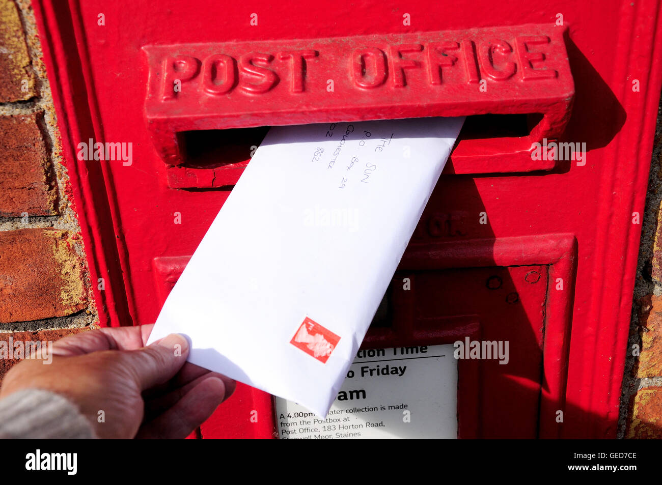 Posting letter in Royal Mail wall pillar box, Stanwell Moor, Surrey, England, United Kingdom - Stock Image