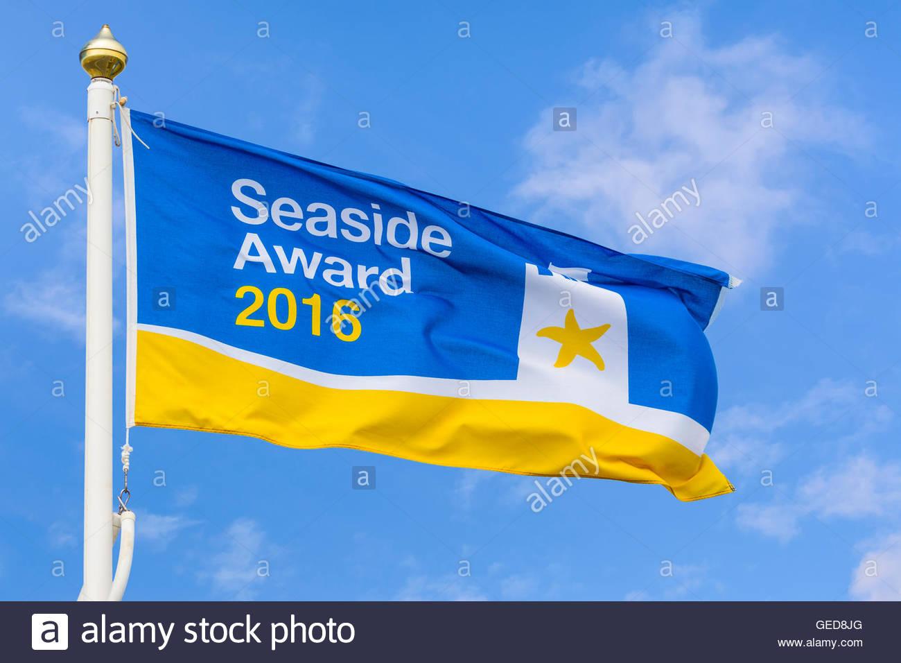 Seaside Award 2016 flag flying against blue sky in Littlehampton, West Sussex, England, UK. - Stock Image