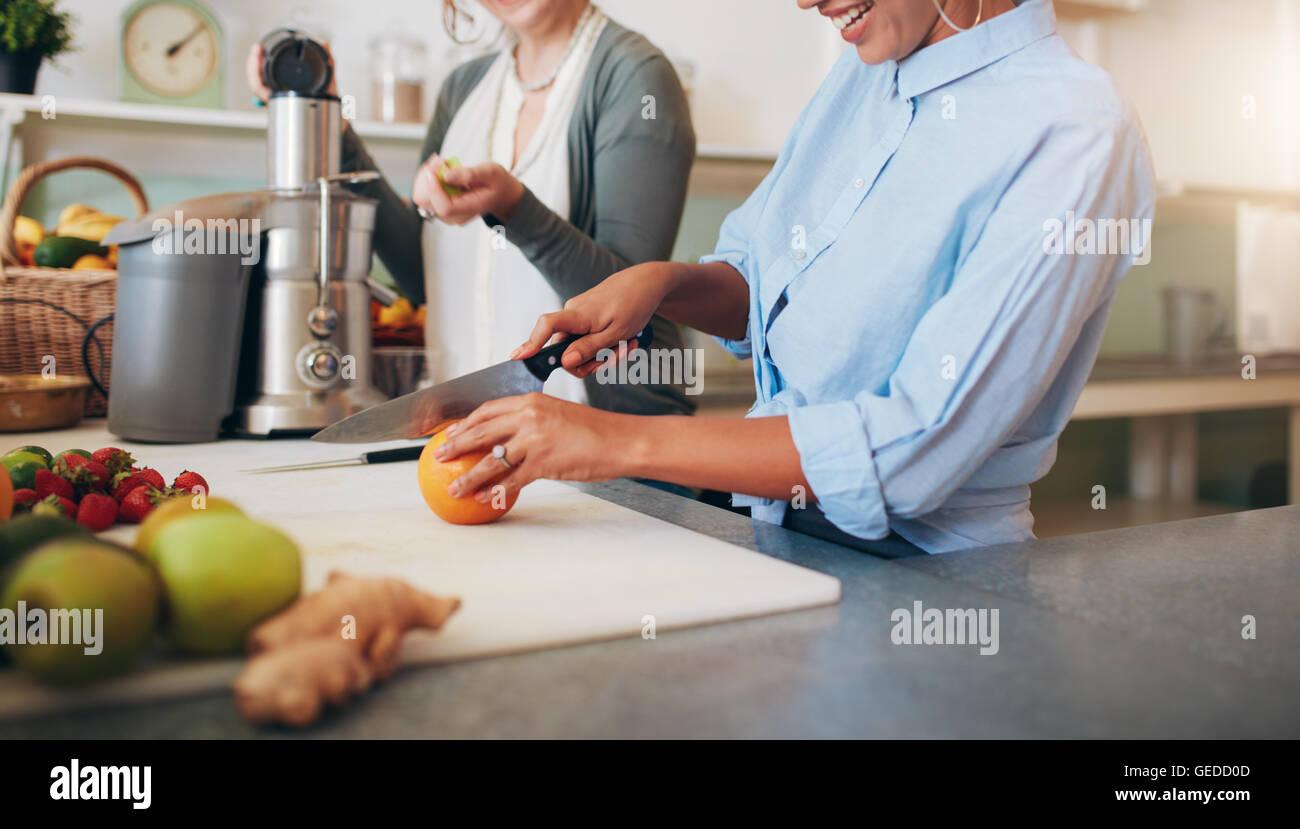 Cropped image of woman cutting an orange. Women at bar counter preparing juice. - Stock Image