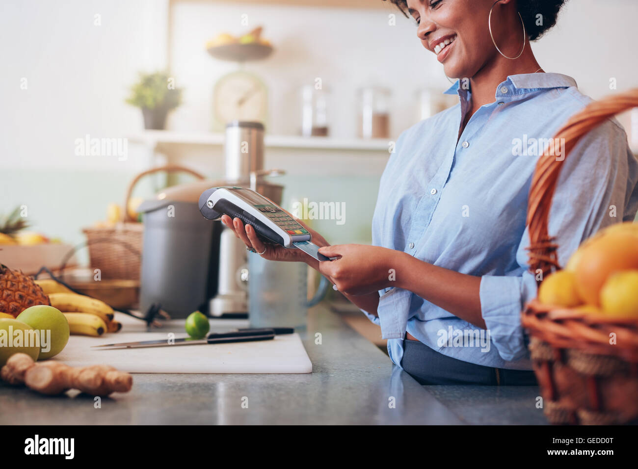 Female employee in a juice bar swiping a credit card in a card reader machine. African woman standing at checkout - Stock Image