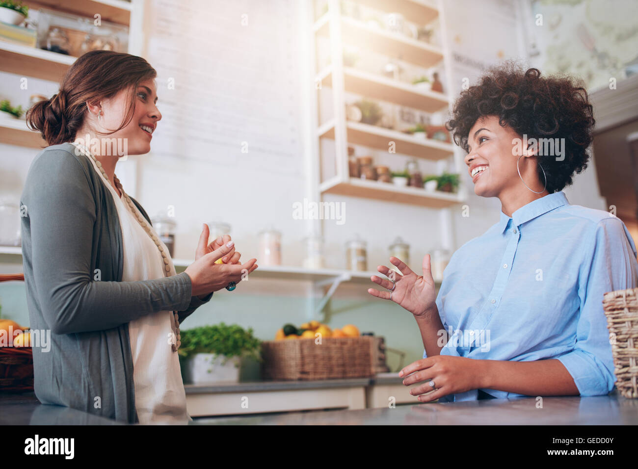 Two happy young female waitress standing behind a bar counter talking to each other. Juice bar partners discussing - Stock Image