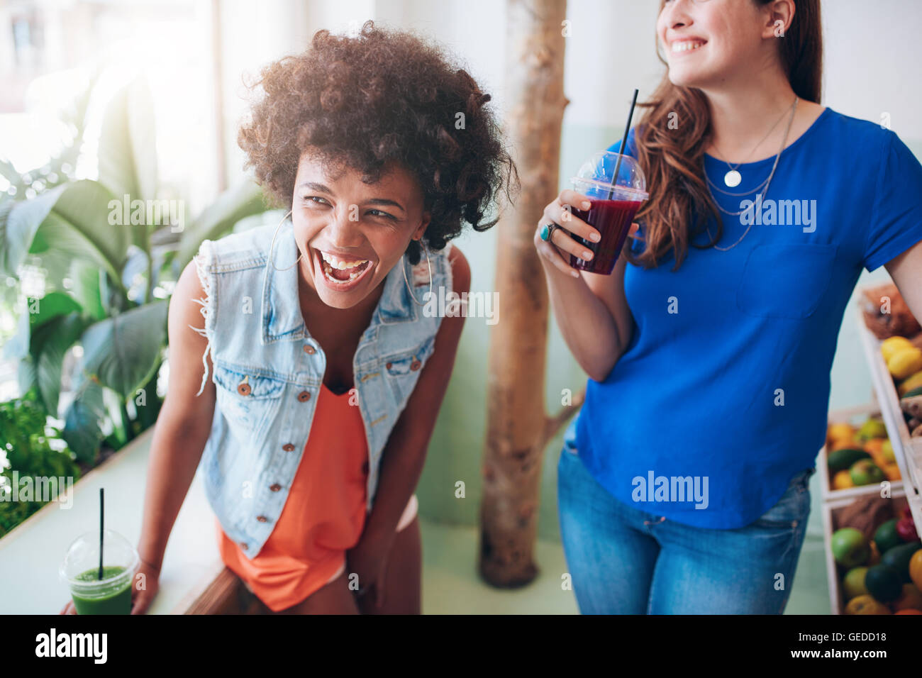 Portrait of cheerful young women at juice bar having a glass of fresh juice. Friends enjoying a juice bar. - Stock Image