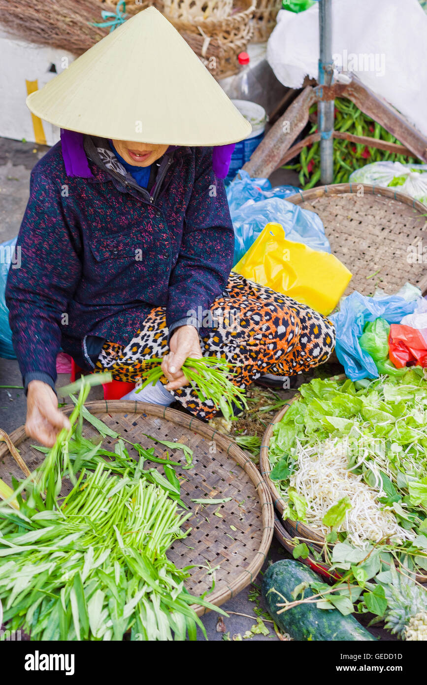 52843169c6f Asian trader in a traditional vietnamese hat selling fresh green garden  stuff in the street market