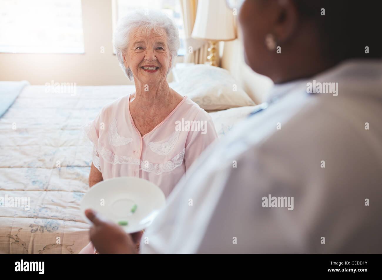 Indoor shot of senior woman sitting on bed and home care nurse giving medication. Caucasian elderly woman smiling. - Stock Image