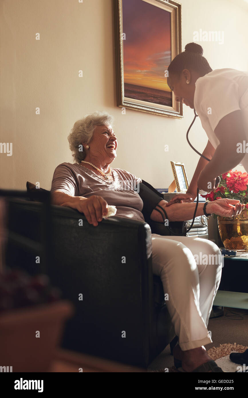 Home caregiver measuring blood pressure of senior patient at home. Female healthcare worker doing routine checkup - Stock Image