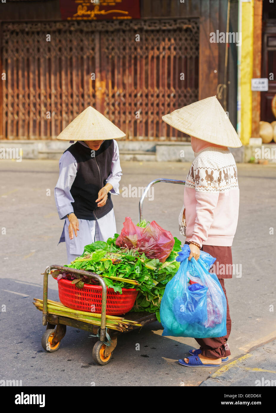 Hoi An, Vietnam - February 17, 2016: Asian buyer and trader in a traditional vietnamese hat selling fresh spinach Stock Photo