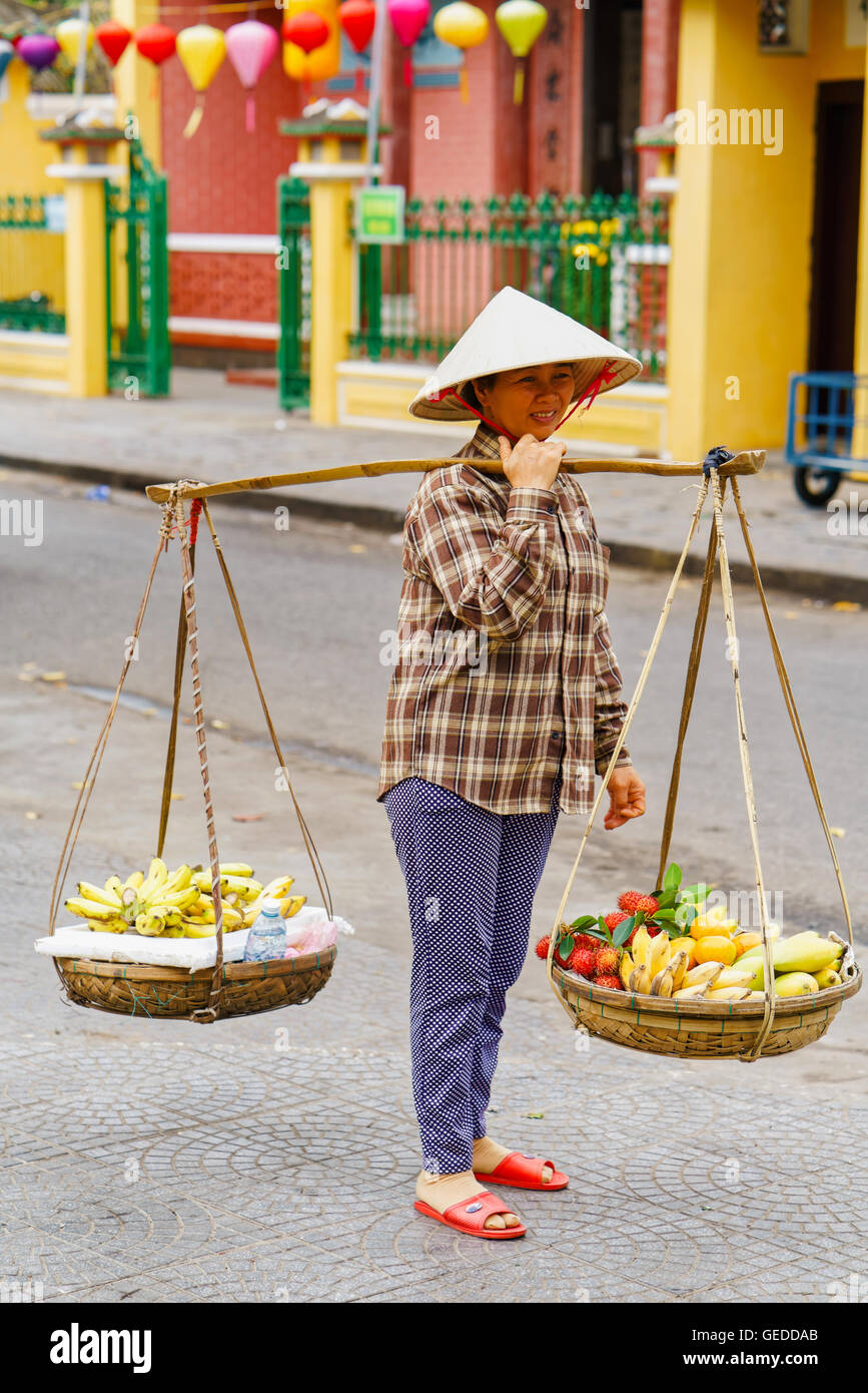 Hoi An, Vietnam - February 17, 2016: Asian woman seller carrying fresh fruit in bowls on her shoulders in the street Stock Photo