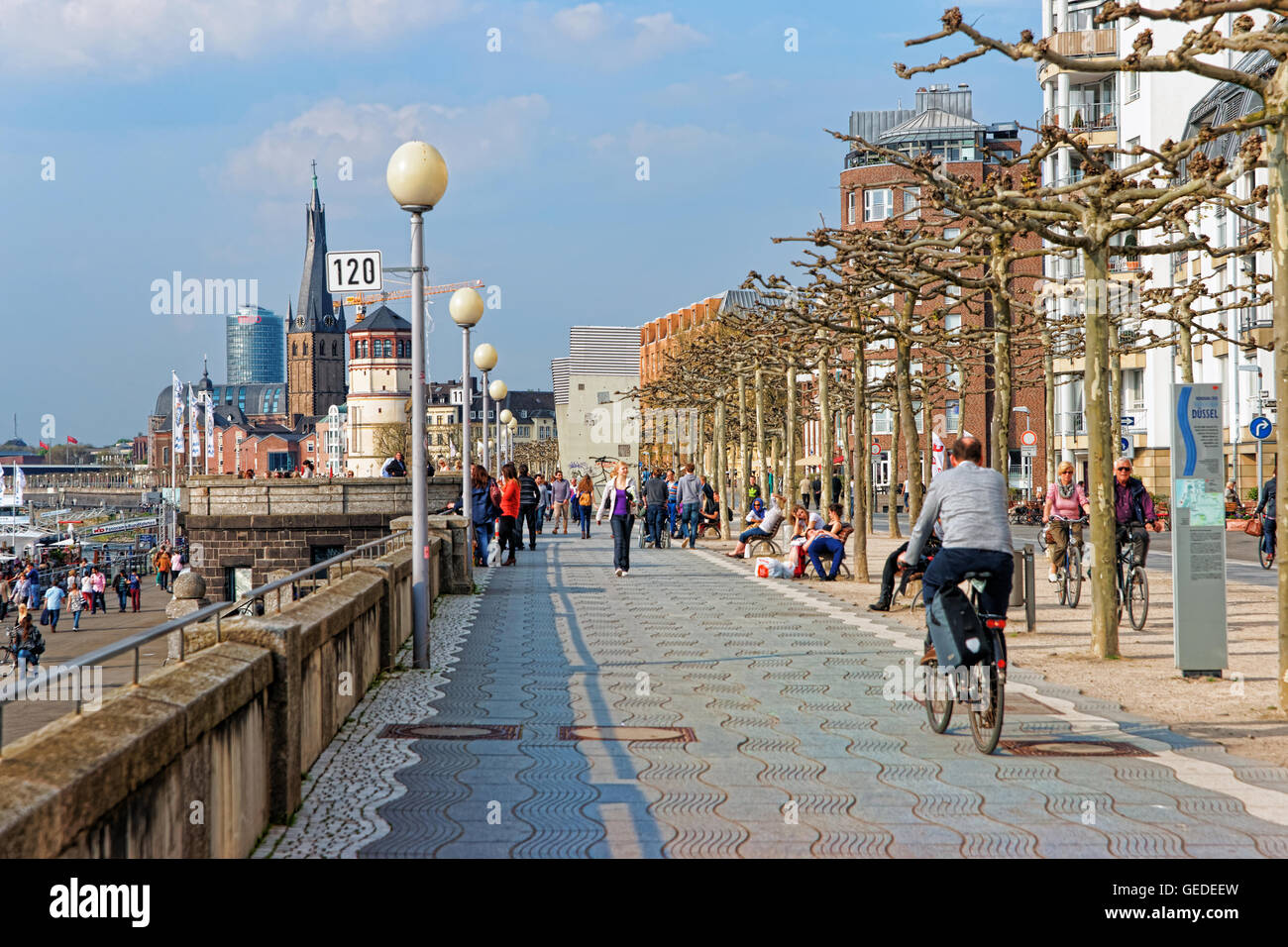 Dusseldorf, Germany - May 3, 2013: Rhine embankment promenade in the Old city center of Dusseldorf in Germany. Tourists nearby. It is the capital of Rhine Westphalia region. Stock Photo