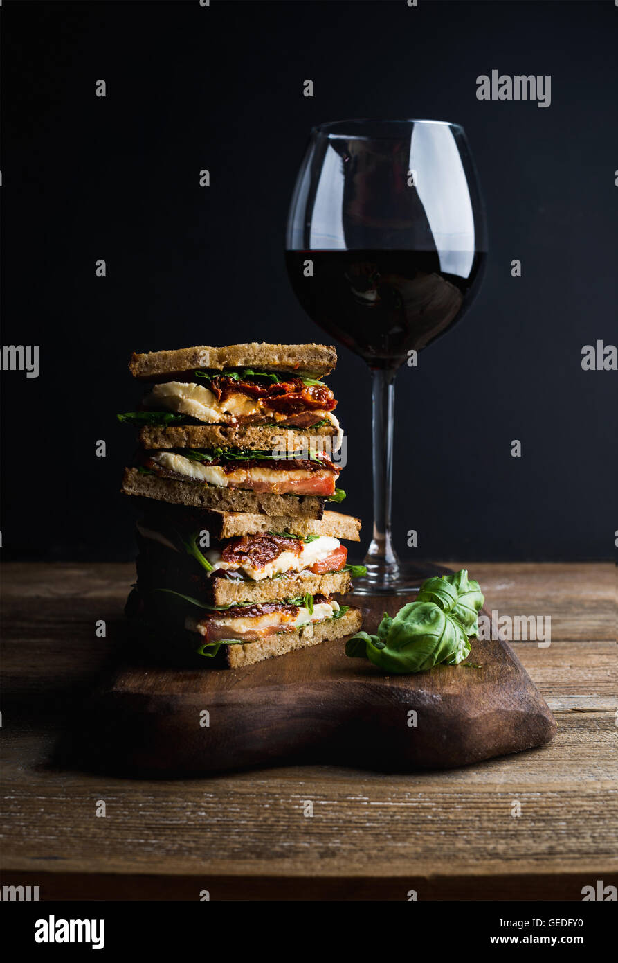 Caprese sandwich or panini and glass of red wine. Whole grain bread, mozzarella, dried tomatoes, basil. Dark background, - Stock Image