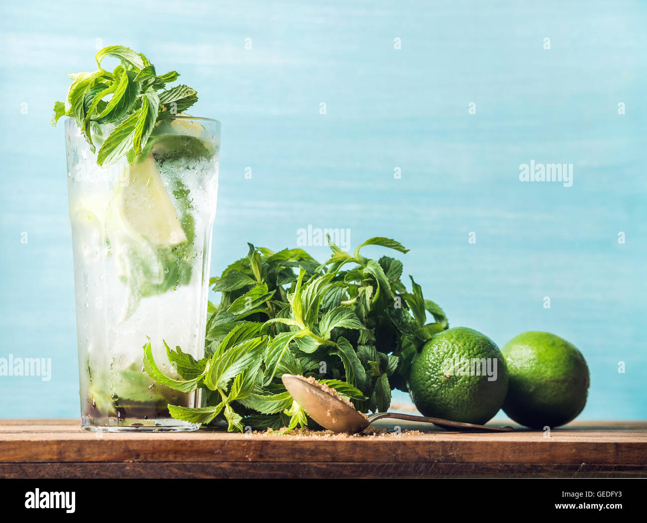 Homemade Mojito cocktail in tall glass with bunch of mint, brown sugar and limes - Stock Image