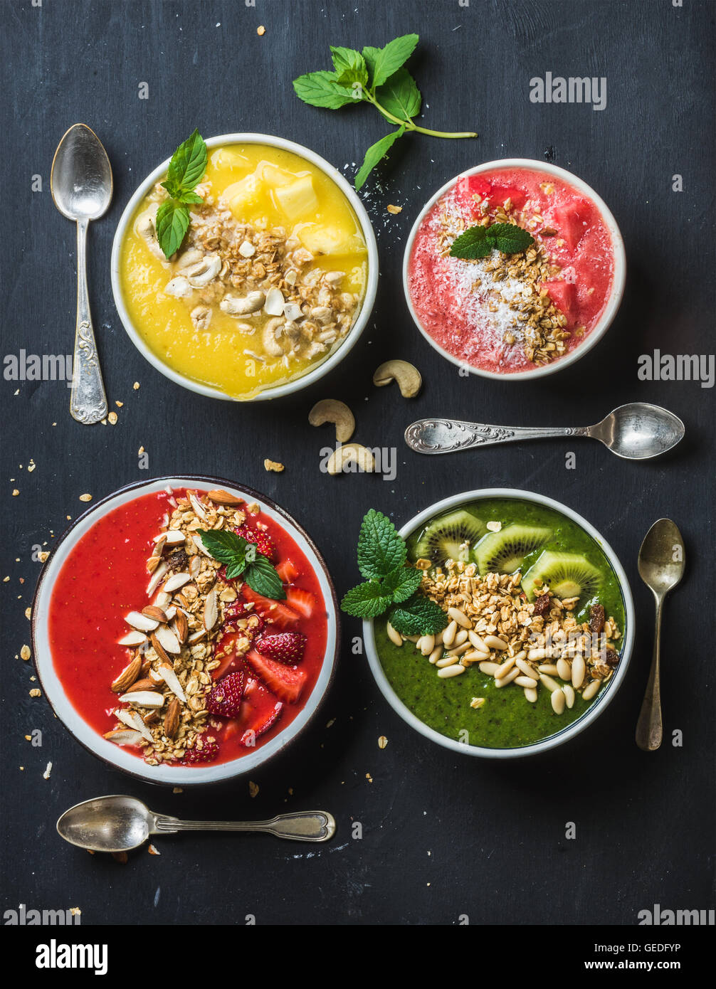 Healthy summer breakfast concept. Colorful fruit smoothie bowls with nuts, oat granola and mint leaves on black - Stock Image